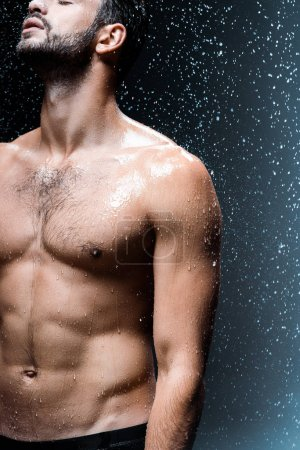 cropped view of shirtless sexy man standing under raindrops on black