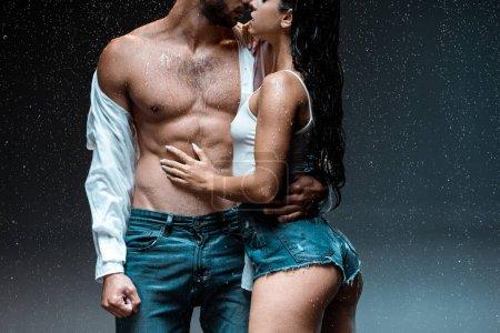 Photo pour Vue recadrée de déshabillé musclé homme debout avec sexy fille sous gouttes de pluie sur noir - image libre de droit