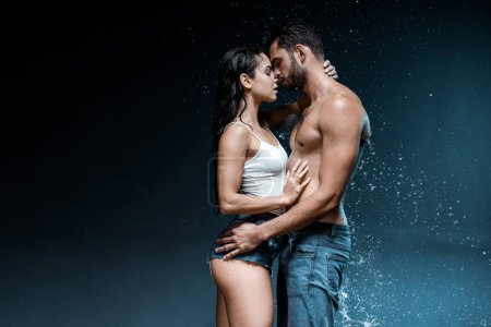 Photo for Sexy shirtless man hugging attractive woman near splash of water on black - Royalty Free Image