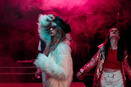 Photo pour Filles dansant dans la boîte de nuit avec la fumée rose de néon - image libre de droit