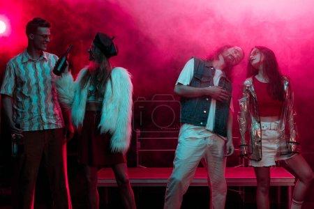 Photo pour Hommes et filles avec de l'alcool dansant dans une boîte de nuit avec de la fumée rose fluo - image libre de droit