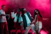 """Постер, картина, фотообои """"men and girls with alcohol dancing in nightclub with pink smoke"""""""