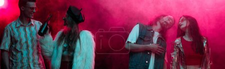 Photo pour Panoramic shot of men and girls with alcohol dancing in nightclub with pink smoke - image libre de droit