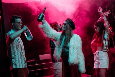 Photo pour Hommes et filles avec la danse d'alcool dans la boîte de nuit avec la fumée rose - image libre de droit