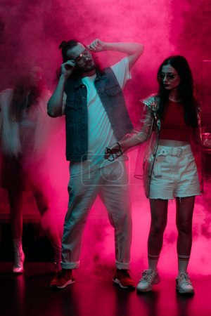 Photo pour Dansant d'homme et de fille dans la boîte de nuit avec la fumée rose de néon - image libre de droit