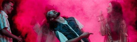 Photo pour Tir panoramique d'hommes et de filles dansant dans la boîte de nuit avec la fumée rose - image libre de droit