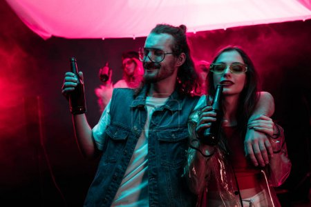 Photo for Beautiful young woman and handsome man with beer in nightclub during rave - Royalty Free Image