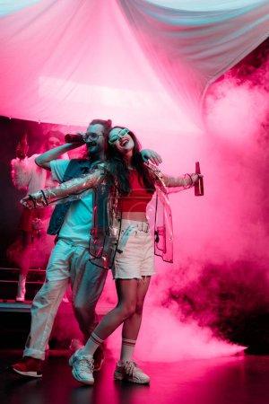 Photo pour Homme heureux et belle danse de fille dans la boîte de nuit avec la fumée rose - image libre de droit
