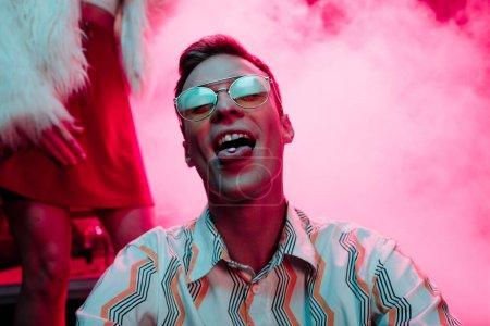 Photo pour Homme dans des lunettes de soleil avec lsd sur la langue dans la boîte de nuit avec la fumée rose - image libre de droit