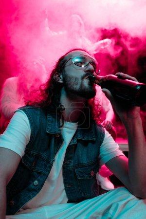 Photo pour Homme dans des lunettes de soleil buvant de l'alcool pendant la rave dans la boîte de nuit - image libre de droit
