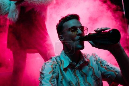 Photo pour Bel homme dans des lunettes de soleil buvant de l'alcool pendant la rave dans la boîte de nuit - image libre de droit