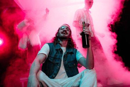Photo pour Homme heureux dans des lunettes de soleil avec la bouteille d'alcool pendant la rave dans la boîte de nuit - image libre de droit