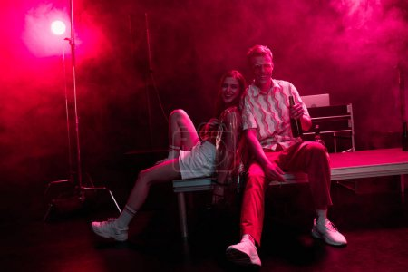 Photo pour Man and young woman sitting together during rave party in nightclub with pink smoke - image libre de droit