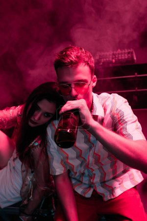 Photo for Man with beer embracing girl in nightclub during rave - Royalty Free Image
