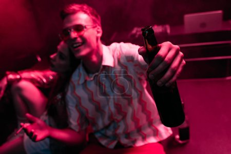Photo pour Homme de sourire avec la bière et la cigarette près de la fille dans la boîte de nuit pendant la rave - image libre de droit