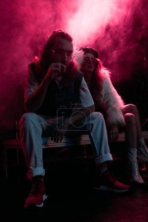 Photo for Man smoking cigarette near young woman during rave party in nightclub with pink smoke - Royalty Free Image