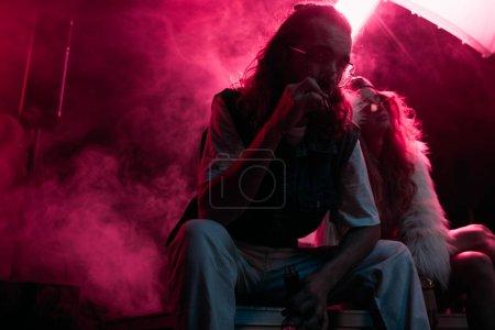 Photo pour Homme fumant la cigarette près de la jeune femme pendant la fête rave dans la boîte de nuit - image libre de droit