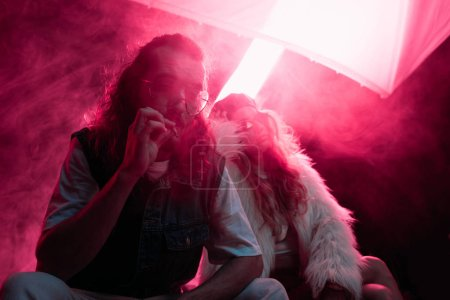 Photo for Man smoking cigarette near young woman during rave party in nightclub - Royalty Free Image