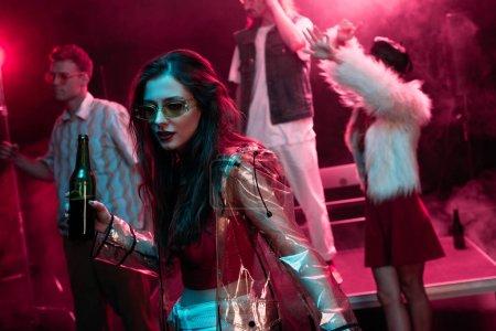 Photo pour Belle fille retenant la bière et dansant dans la boîte de nuit avec la fumée rose - image libre de droit