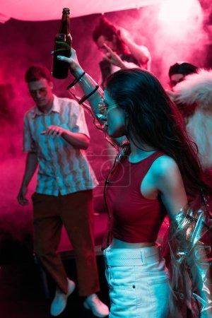 Photo pour Belle fille retenant la bière et dansant dans la boîte de nuit avec la fumée rose de néon - image libre de droit