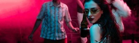 Photo pour Tir panoramique de la belle fille retenant la bière et dansant dans la boîte de nuit avec la fumée rose - image libre de droit