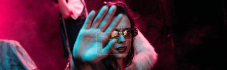 Photo pour Plan panoramique de fille dans des lunettes de soleil montrant la main à la caméra dans la boîte de nuit pendant la fête rave - image libre de droit