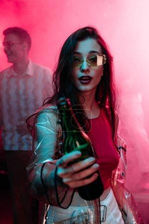 Photo pour Fille dans des lunettes de soleil avec la bouteille d'alcool pendant la rave dans la boîte de nuit - image libre de droit