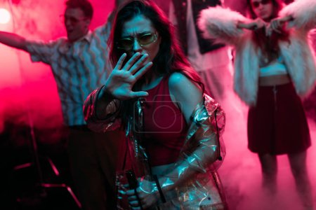 Photo pour Girl Gesturing with hand while dancing in nightclub with pink smoke - image libre de droit