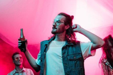 Photo pour Bel homme retenant la bière dans la boîte de nuit et la danse pendant la rave - image libre de droit
