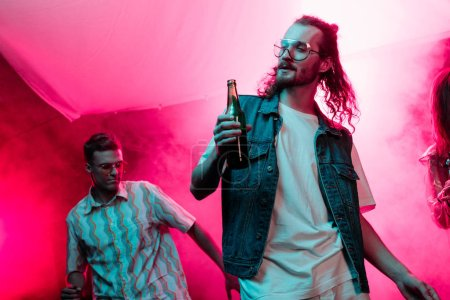 Photo pour Handsome man holding beer in nightclub and dancing during rave - image libre de droit