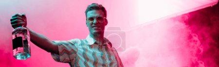 Photo pour Plan panoramique de bel homme avec bouteille d'alcool pendant la rave dans la boîte de nuit - image libre de droit