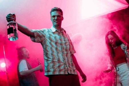 Photo pour Bel homme avec bouteille d'alcool pendant la rave dans la boîte de nuit - image libre de droit