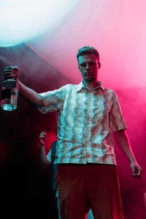 Photo pour Homme en lunettes de soleil avec bouteille d'alcool pendant la rave dans la boîte de nuit - image libre de droit