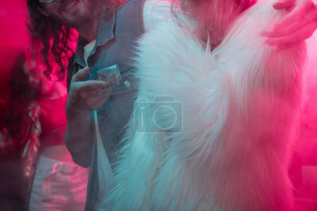 Photo for Cropped view of man giving weed in plastic zipper bag to girl in nightclub - Royalty Free Image