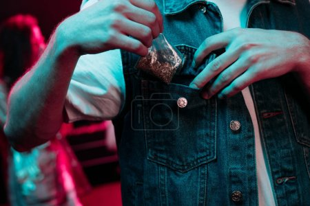 Photo for Cropped view of man putting in pocket marijuana in nightclub - Royalty Free Image