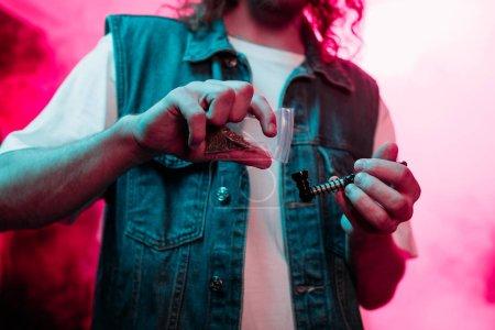 Photo pour Vue cultivée de l'homme mettant la marijuana dans la pipe de tabagisme dans la boîte de nuit - image libre de droit