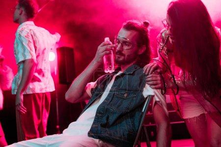 Photo pour Fille regardant malade homme assis avec bouteille d'eau dans la boîte de nuit - image libre de droit