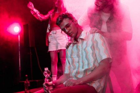 Photo pour Homme vérifiant sur l'homme malade assis avec une bouteille d'eau dans la boîte de nuit - image libre de droit