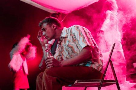 Photo pour Homme assis avec une bouteille d'eau dans une boîte de nuit et touchant la tête - image libre de droit