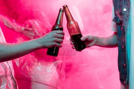 Photo pour Vue recadrée des hommes cliquetis avec des bouteilles de bière dans la boîte de nuit - image libre de droit