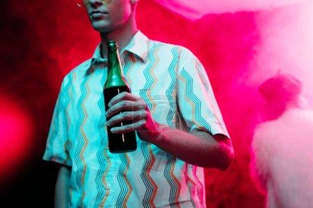 Photo pour Vue recadrée de l'homme avec bouteille d'alcool pendant la rave dans la boîte de nuit - image libre de droit