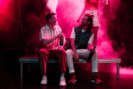 Photo pour Hommes assis avec de la bière et parler dans la boîte de nuit pendant la rave - image libre de droit
