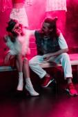 "Постер, картина, фотообои ""man hugging young woman during rave party in nightclub"""