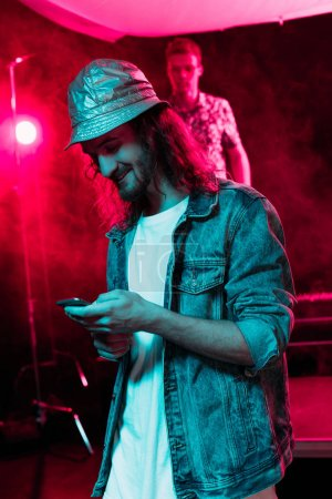 Photo pour Homme utilisant smartphone pendant la fête rave dans la boîte de nuit - image libre de droit