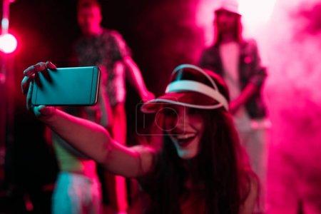 Photo pour Fille heureuse prenant le selfie sur le smartphone pendant la partie de rave dans la boîte de nuit - image libre de droit