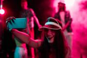 "Постер, картина, фотообои ""happy girl taking selfie on smartphone during rave party in nightclub"""