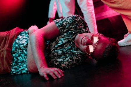 Photo pour Malade dans des lunettes de soleil couché sur le sol dans une boîte de nuit - image libre de droit