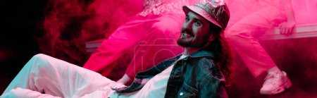 Photo for Panoramic shot of smiling man lying on floor in nightclub during rave party with pink smoke - Royalty Free Image