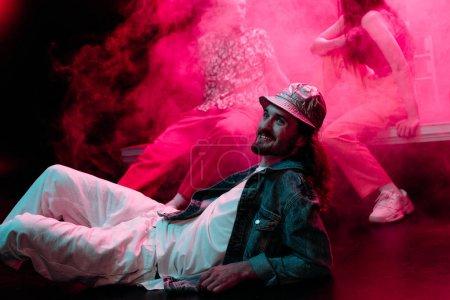 Photo pour Homme de sourire se trouvant sur l'étage dans la boîte de nuit pendant la partie rave avec la fumée rose - image libre de droit
