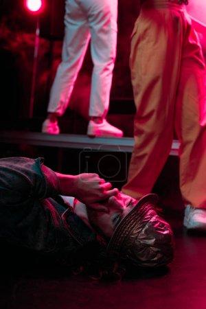 Photo pour Malade couché sur le sol dans une boîte de nuit avec un éclairage dramatique et couvrant la bouche - image libre de droit